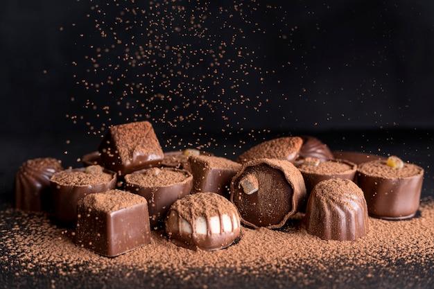 Alto angolo di caramelle al cioccolato con cacao in polvere