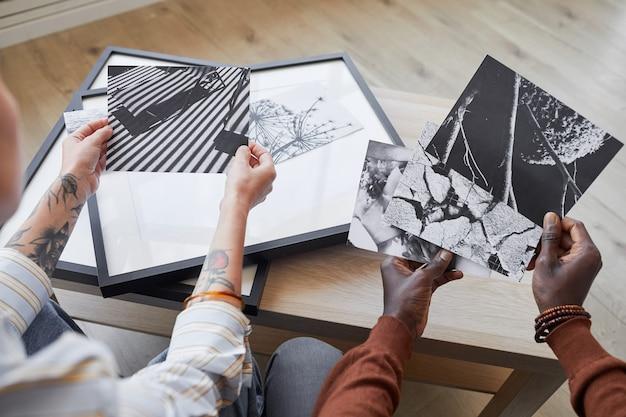 Elevato angolo ravvicinato di due giovani moderni discutendo di immagini in bianco e nero mentre si sceglie la grafica per l'arredamento di interni,