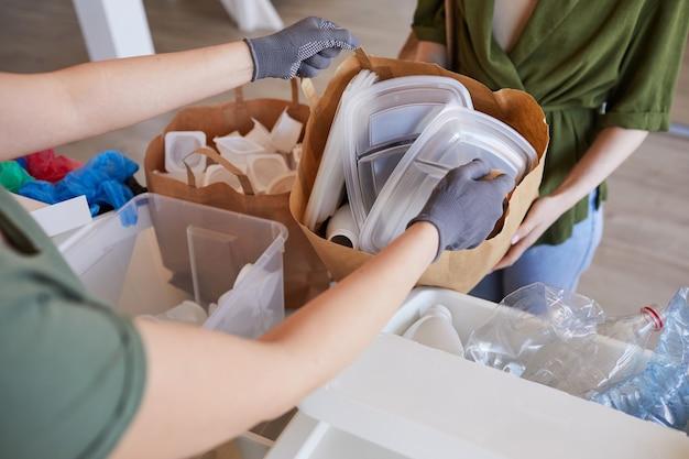 Primo piano alto angolo di due persone che smistano oggetti di plastica a casa, preparando i rifiuti per il riciclaggio