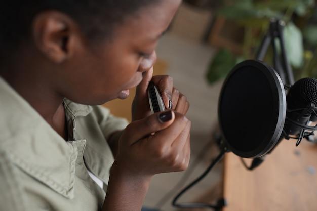 Alto angolo primo piano di giovane donna afro-americana che suona l'armonica al microfono durante la composizione di musica in studio di registrazione domestica, copia dello spazio