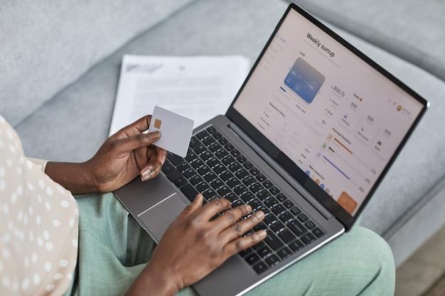 Primo piano ad alto angolo di una giovane donna afro-americana che utilizza laptop con servizio di banking online sullo schermo, spazio di copia