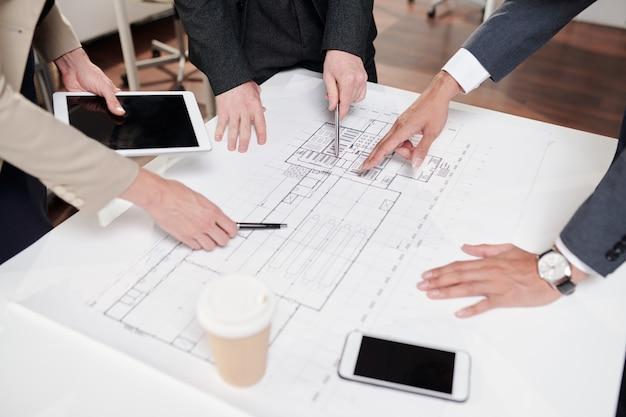 Primo piano alto angolo del team aziendale che punta a piani e bozze mentre si discute del progetto di ingegneria durante la riunione in ufficio, copia dello spazio