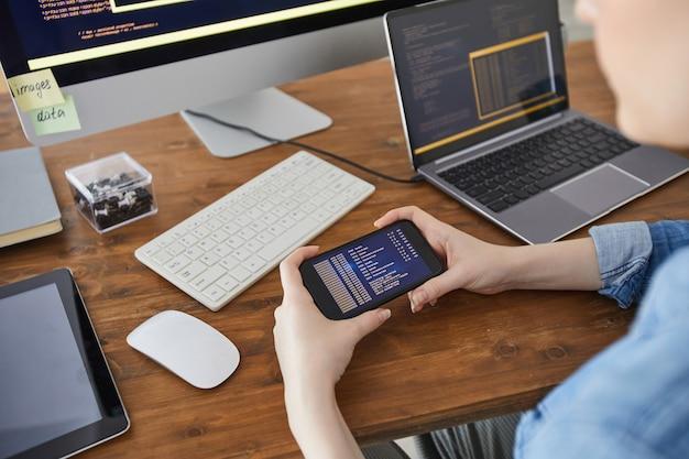 Primo piano di alto angolo delle mani femminili che tengono smartphone con codice sullo schermo mentre si lavora alla scrivania in ufficio, concetto di sviluppatore it femminile, spazio di copia