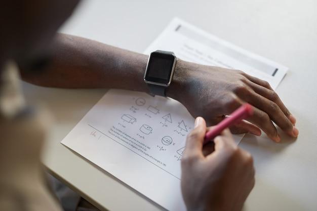 Primo piano ad alto angolo di un ragazzo afroamericano irriconoscibile che scrive sul taccuino mentre fa il test di matematica a scuola, si concentra su smartwatch, copia spazio