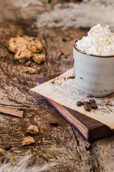 Caffè ad angolo alto con latte e panna montata con biscotto
