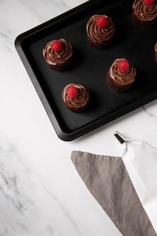 Alto angolo di deliziosi cupcakes al cioccolato con lampone