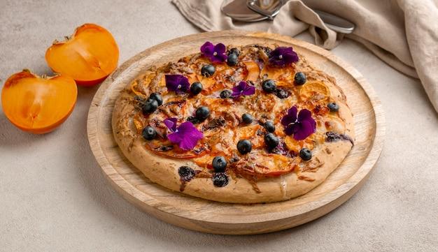 Alto angolo di deliziosa pizza cotta con cachi e petali di fiori