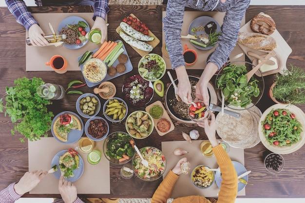 Alto angolo di delizioso tavolo vegetariano festivo e persone che mangiano
