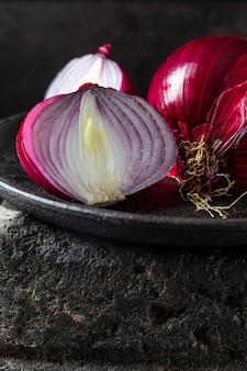 Cipolle rosse deliziose di alto angolo sulla zolla