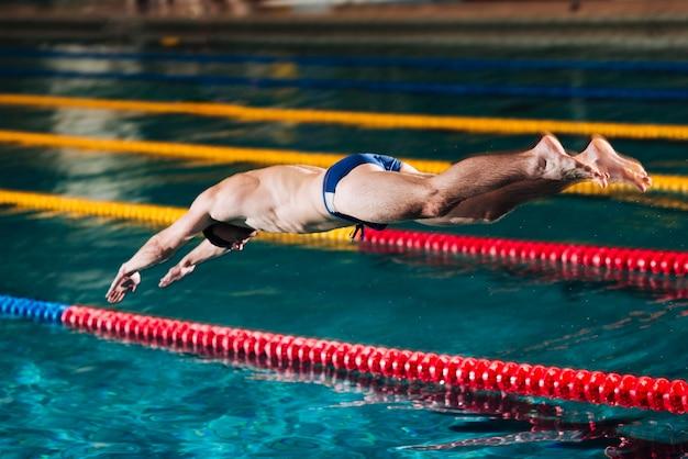 Salto di tuffo dell'angolo alto nella piscina