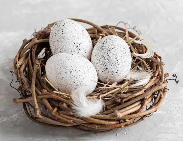 Alto angolo di uova per pasqua nel nido di uccelli con piume