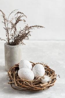 Alto angolo di uova di pasqua nel nido con fiori in vaso