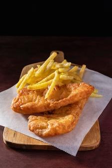 Alto angolo di pesce e patatine fritte sul tagliere