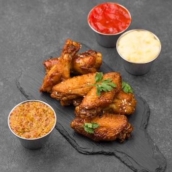 Alto angolo di pollo fritto con varietà di salse su ardesia