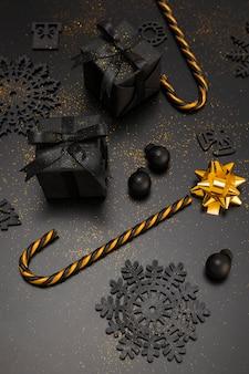 Alto angolo di bastoncino di zucchero dorato e regali di natale
