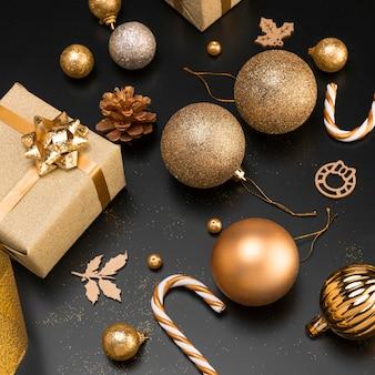 Alto angolo di ornamenti natalizi dorati con presente e zucchero filato
