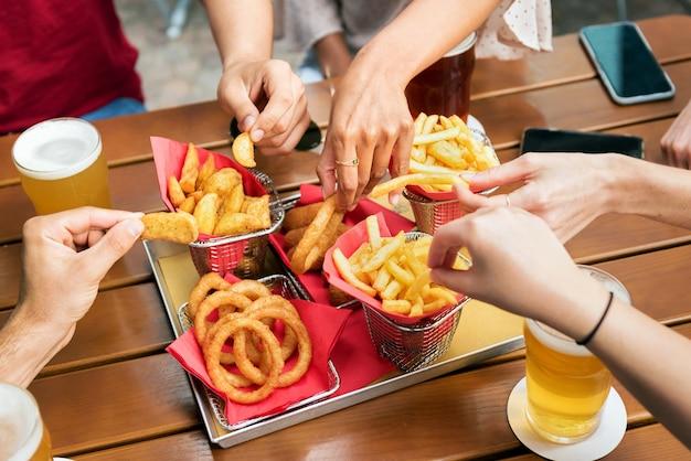 Alto angolo di un gruppo di amici irriconoscibili del raccolto che prendono patatine fritte e anelli di cipolla croccanti dal vassoio mentre si riuniscono e bevono birra al pub