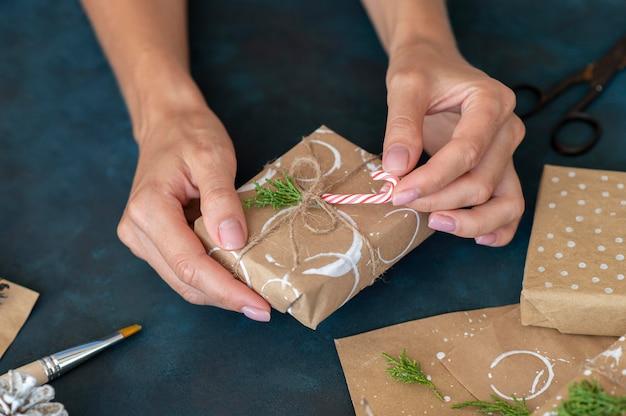 Alto angolo delle mani che decorano il regalo di natale con il bastoncino di zucchero