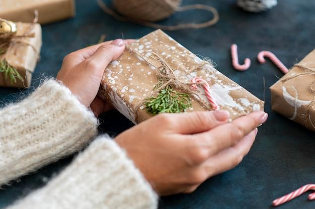 Alto angolo delle mani che tengono il regalo di natale con la decorazione del bastoncino di zucchero