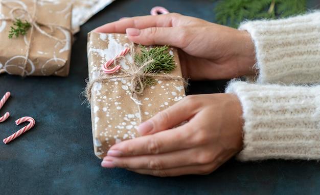 Alto angolo delle mani che tengono il regalo di natale con il bastoncino di zucchero