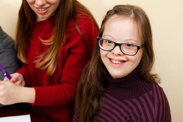Angolo alto della ragazza felice con la posa di sindrome di down
