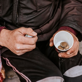 Alto angolo di senzatetto con tazza e monete