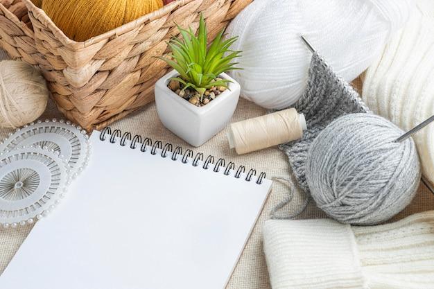 Angolo alto di lavoro a maglia con filato e taccuino