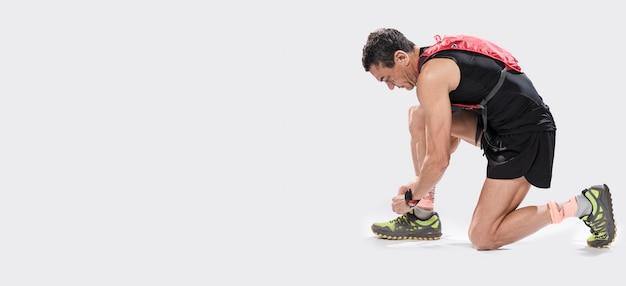 Uomo alto angolo che lega i lacci delle scarpe