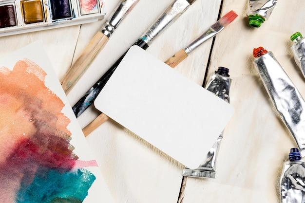 Alto angolo di pennelli con carta e vernice