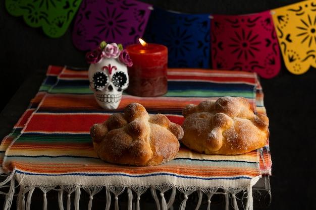Angolo alto di pan de muerto con candela e teschio