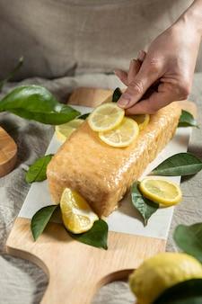 Angolo alto del pasticcere che aggiunge fette di limone alla copertura della torta
