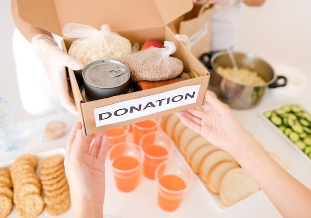 Alto angolo di persona che distribuisce donazioni di cibo