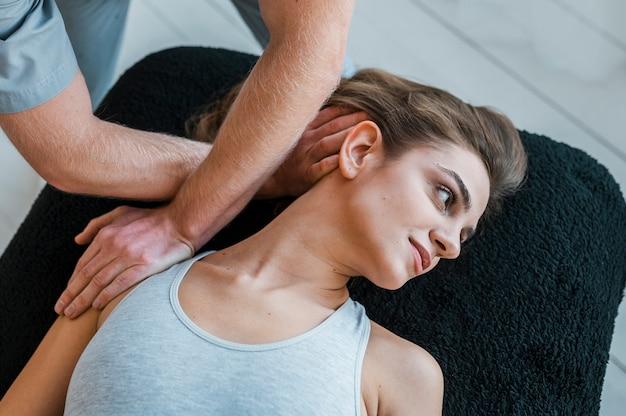 Alto angolo di fisioterapista che esegue esercizi sul paziente femminile