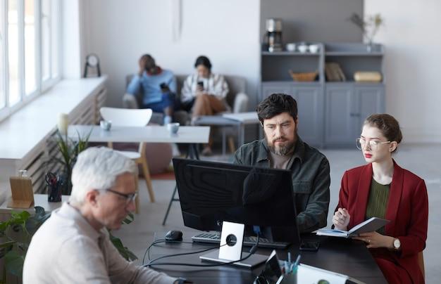 Ritratto ad alto angolo di un manager barbuto che parla con una collega durante la riunione al tavolo nell'interno dell'ufficio bianco