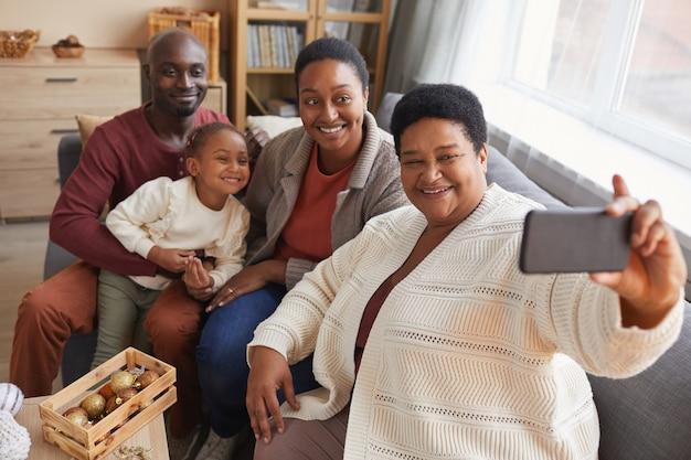 Ritratto di alto angolo di grande famiglia afro-americana felice che cattura foto selfie mentre vi godete il natale a casa insieme