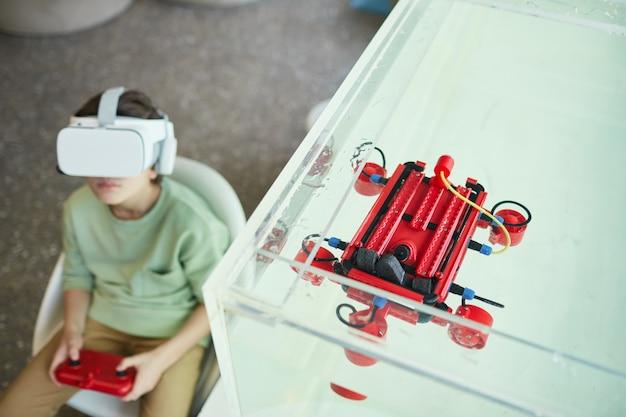 Ritratto ad alto angolo di un ragazzo che indossa l'auricolare vr durante l'utilizzo di una barca robotica nel laboratorio della scuola, spazio di copia