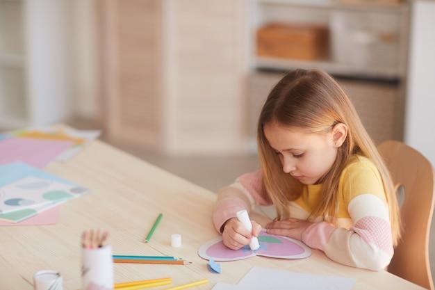 Ritratto di alto angolo della bambina sveglia che fa carta fatta a mano per la festa della mamma mentre è seduto al tavolo in interni domestici accoglienti, spazio di copia
