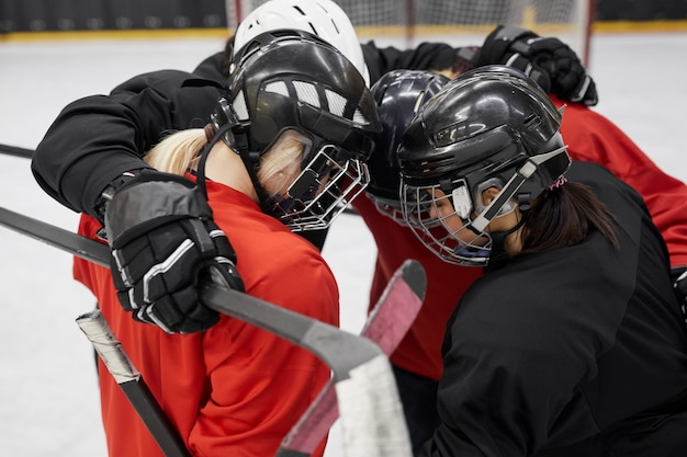 Ritratto di alto angolo della squadra di hockey femminile che stringe a sé per la motivazione prima della partita sportiva