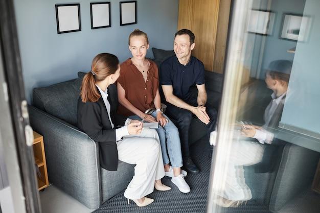 Ritratto ad alto angolo di agente immobiliare femminile che firma un contratto con una giovane coppia che acquista una nuova casa, copia spazio