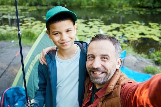 Ritratto di alto angolo del padre felice che prende la foto del selfie con il figlio mentre si gode la battuta di pesca insieme, lo spazio della copia