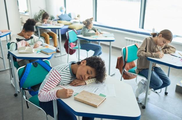 Ritratto ad alto angolo di un ragazzo di razza mista che dorme alla scrivania in aula scolastica, copia spazio