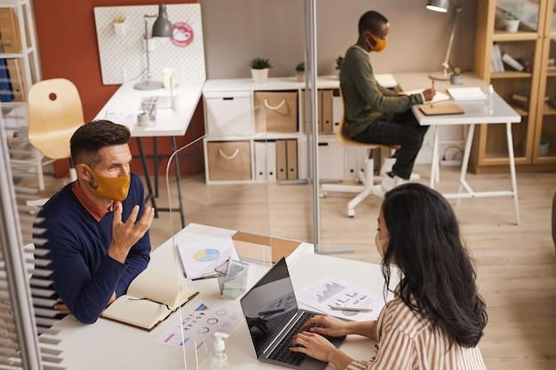 Ritratto di alto angolo dell'uomo maturo moderno che indossa la maschera e parlando con un collega attraverso il pannello di vetro durante la riunione di lavoro post pandemia, spazio di copia