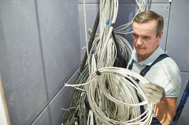 Ritratto di alto angolo dell'elettricista senior che collega i cavi nell'armadietto dei cavi durante il rinnovamento della casa, spazio della copia