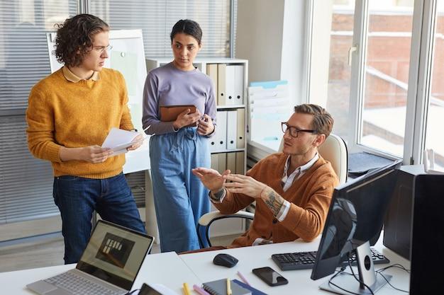 Ritratto ad alto angolo del capo squadra che dà istruzioni ai colleghi mentre collabora al progetto nello studio di sviluppo it, copia spazio