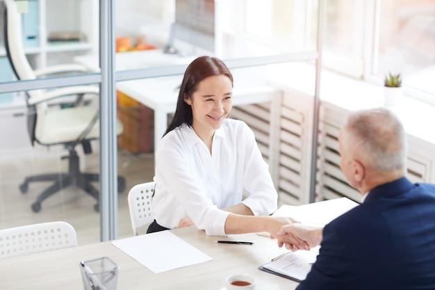 Ritratto di alto angolo di giovane donna di affari asiatica che sorride felicemente mentre stringe la mano con l'uomo anziano attraverso il tavolo in ufficio