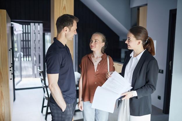 Ritratto ad alto angolo di giovane coppia che parla con un agente immobiliare mentre acquista una nuova casa, copia spazio