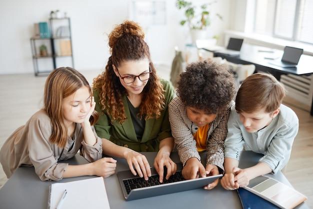 Ritratto ad alto angolo di una giovane insegnante che utilizza il computer con un gruppo eterogeneo di bambini