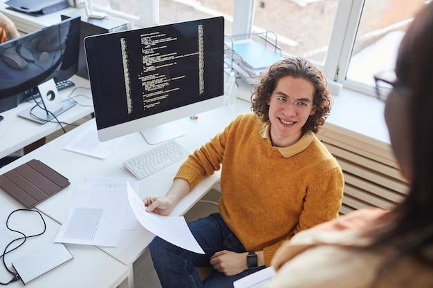 Ritratto ad alto angolo di giovane uomo dai capelli lunghi che sorride al collega mentre discute il progetto di sviluppo software in ufficio, copia spazio