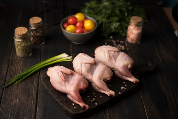 Pollo crudo dell'angolo alto sul bordo di legno con i condimenti