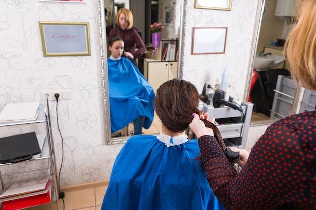 Vista posteriore dell'angolo alto dello stilista che pettina i capelli della donna castana con i capelli bagnati che si siede nella sedia nel salone - riflessione dello stilista e del cliente nello specchio del salone sullo sfondo